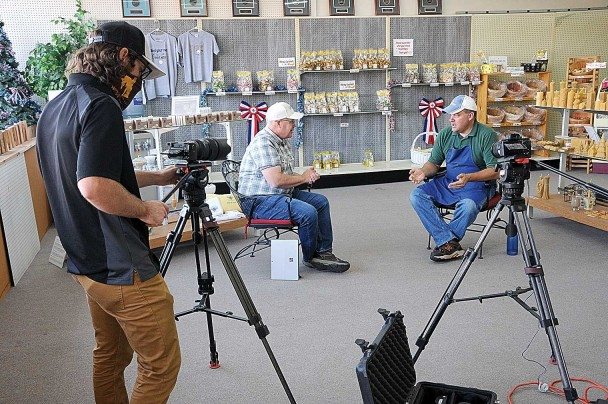 WyomingPBS videographer Kyle Duba operates a camera while public affairs producer Craig Blumenshine interviews Queen Bee Gardens confectioner Jason Zeller (right) Friday morning at the storefront in Lovell.