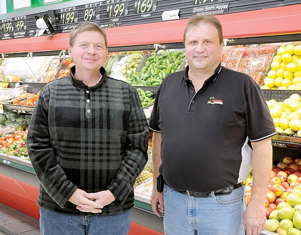 Red Apple store and produce manager Mike Allred, right, visits with new owner Darin Hill on Monday as Hill was in town to oversee the transition to new ownership and operations.