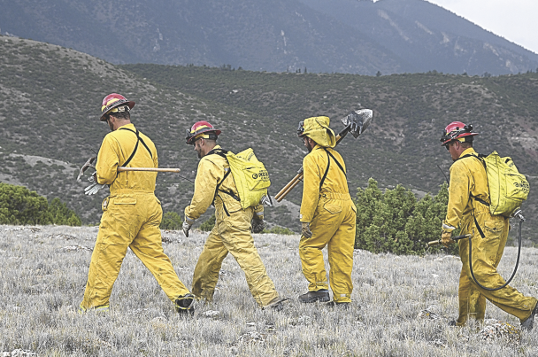 David Peck photo   Lovell volunteer firemen (l-r) Lynn Hitz, Kyle Leithead, Chris Sawaya and Jacob Bassett strike out to attack the fire just north of the Ewing-Snell Ranch in the Bighorn Canyon National Recreation Area Saturday afternoon. The four, joined by a federal helicopter crew and two other Lovell firemen, quickly contained the blaze.