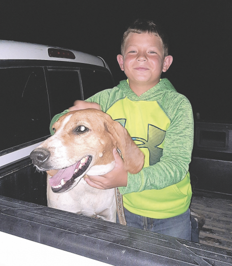courtesy photo     Derek Hedges holds family dog Ace after rescuing the dog from a culvert on Road 5 west of Cowley.